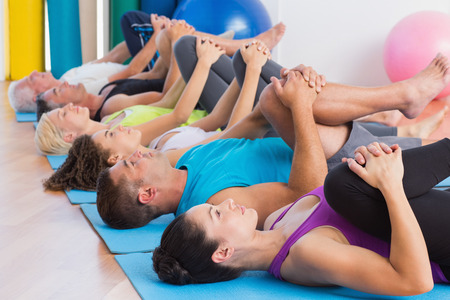 Side view of men and women stretching legs on exercise mats at gym Stock Photo