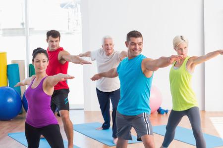 guerrero: Hombres y mujeres que realizan guerrero Fit plantean en clase de yoga Foto de archivo