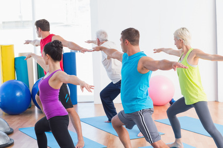 Fit men and women doing warrior pose in yoga class
