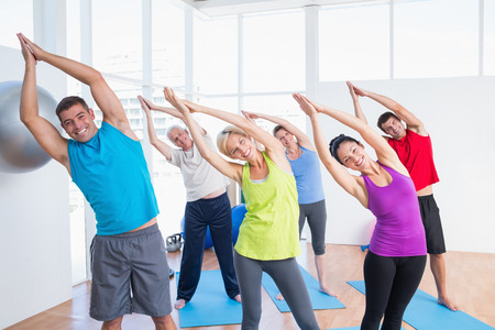 Portrait of happy people doing stretching exercise in yoga class