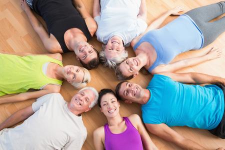 holzboden: Hohe Winkelsicht der gl�cklichen Menschen, die im Kreis auf Hartholzfu�boden im Fitness-Studio