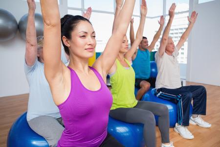 manos levantadas: Las personas en forma que se sientan en las bolas del ejercicio con las manos levantadas en clase de gimnasia