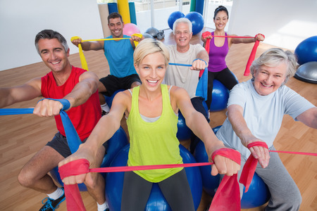 Portrait of happy men and women on fitness balls exercising with resistance bands in gym class