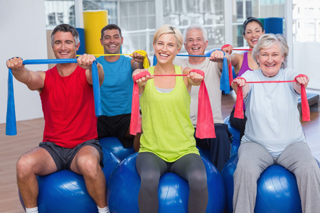 relaxation exercise: Portrait of happy people on fitness balls exercising with resistance bands in gym class Stock Photo