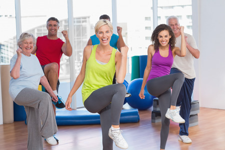 Portrait of smiling people doing power fitness exercise at fitness studio Foto de archivo