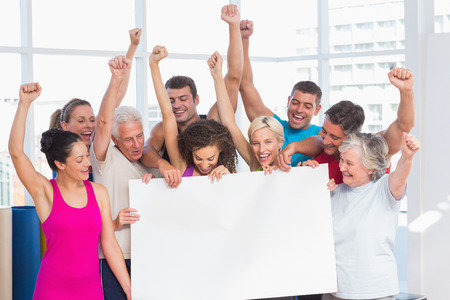 Excited fit people holding blank billboard against window at gym