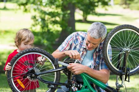 familia feliz: Padre y su hijo que fijan una bici en un día soleado