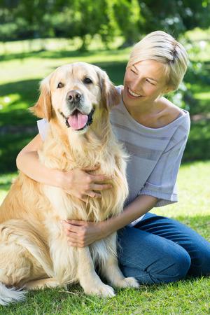 femme blonde: Blonds heureux embrassant son chien dans le parc sur une journ�e ensoleill�e Banque d'images