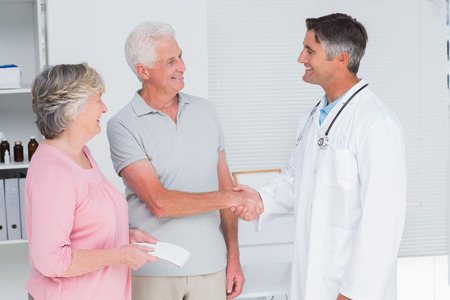 Happy senior couple visiting doctor in clinic photo