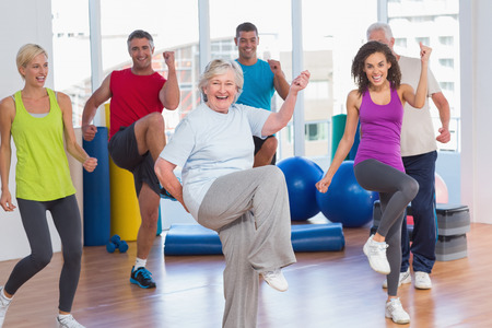 senior friends: Portrait of smiling people doing power fitness exercise at fitness studio Stock Photo