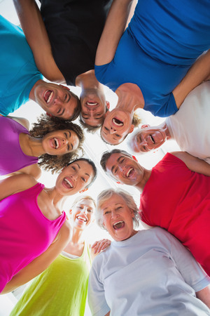 huddle: Low angle portrait of cheerful people forming huddle at gym