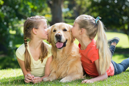 love park: Sisters kissing their dog in the park on a sunny day Stock Photo