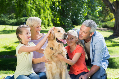 Happy family petting their dog in the park on a sunny day