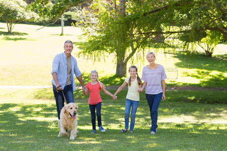 Happy family walking in the park with their dog on a sunny day Banque d'images