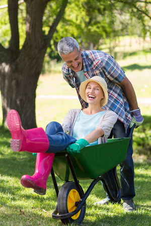 Happy couple playing with a wheelbarrow on a sunny day photo