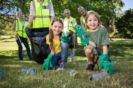 altruism: Familia feliz recogida de basura en un día soleado
