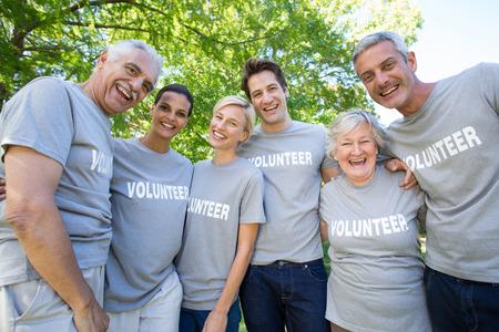 Gelukkig vrijwilliger gezin lachend naar de camera op een zonnige dag Stockfoto