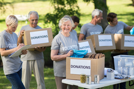 outdoor event: Happy family holding donations boxes on a sunny day
