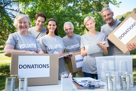 volunteering: Happy volunteer family holding donation boxes on a sunny day