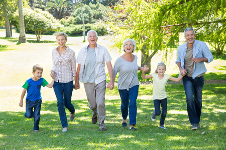 Happy family running in the park on a sunny day Stock Photo