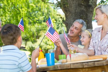 familia pic nic: Familia feliz que tiene comida campestre y sosteniendo la bandera estadounidense en un d�a soleado