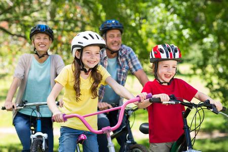 niños en bicicleta: Familia feliz en su bicicleta en el parque en un día soleado Foto de archivo