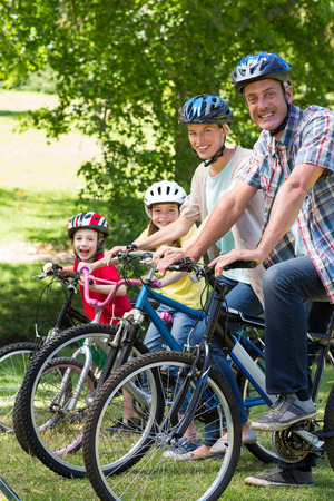 lifestyle caucasian: Happy family on their bike at the park on a sunny day Stock Photo
