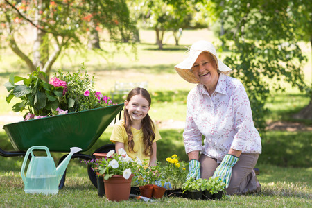 gardening gloves: Happy grandmother with her granddaughter gardening on a sunny day