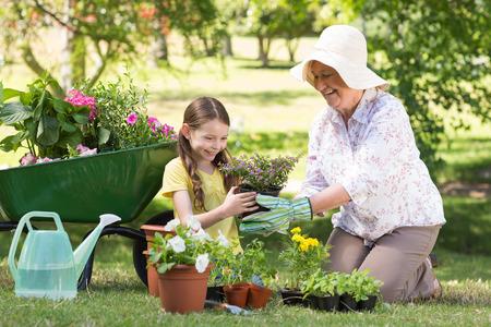 Gelukkig grootmoeder met haar kleindochter tuinieren op een zonnige dag