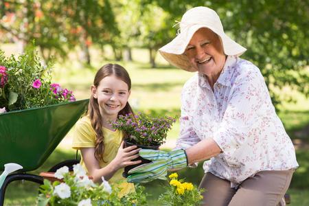 abuelos: Abuela feliz con su nieta de jardinería en un día soleado