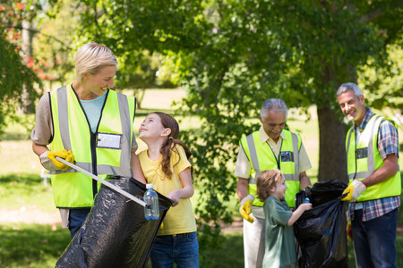 community people: Happy family collecting rubbish on a sunny day