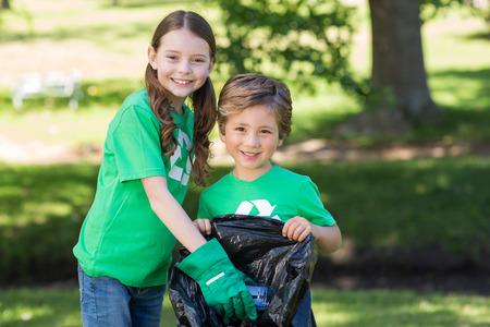niños reciclando: Hermanos felices de recolección de basura en un día soleado Foto de archivo