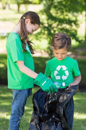 ni�os reciclando: Hermanos felices de recolecci�n de basura en un d�a soleado Foto de archivo