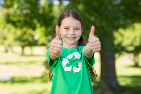 recycle: Happy little girl in green with thumbs up on a sunny day Stock Photo