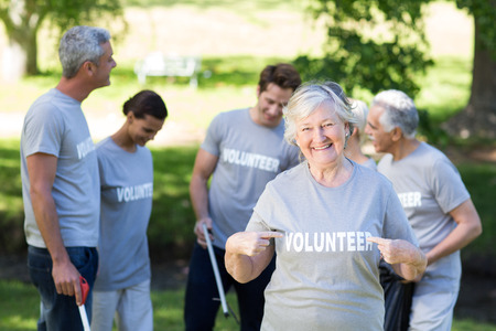 volunteer point: Happy volunteer grandmother with thumbs up on a sunny day