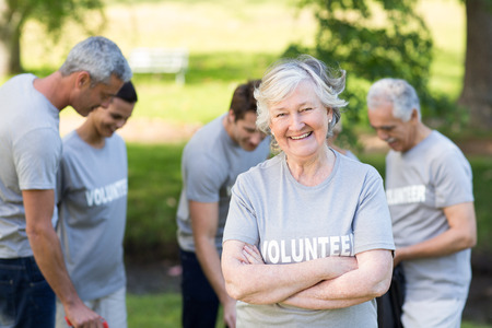 volunteering: Happy volunteer grandmother smiling at camera on a sunny day Stock Photo