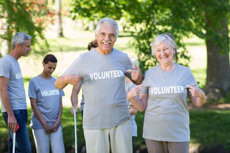 altruismo: Voluntario feliz pareja senior sonriendo a la c�mara en un d�a soleado Foto de archivo
