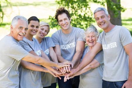 altruismo: Familia voluntario feliz que pone sus manos juntas en un d�a soleado