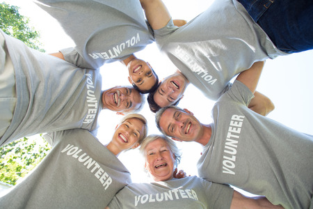 Happy volunteer family looking down at the camera on a sunny day Foto de archivo
