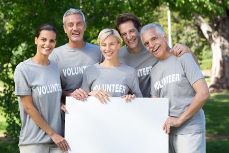 altruismo: Familia voluntario feliz sosteniendo un espacio en blanco en un d�a soleado Foto de archivo