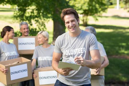 volunteer: Happy volunteer man writing in clipboard on a sunny day Stock Photo