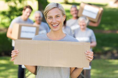 altruismo: Voluntario feliz rubia celebraci�n en blanco en un d�a soleado