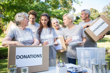 charity person: Happy volunteer family holding donation boxes on a sunny day