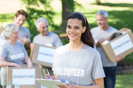 volunteer: Smiling volunteer brunette writing on cipboard on a sunny day Stock Photo