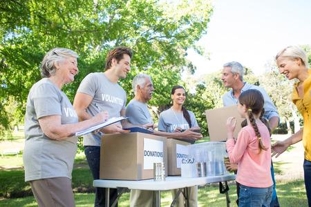 Gelukkig vrijwilliger familie scheiden van donaties propt op een zonnige dag Stockfoto