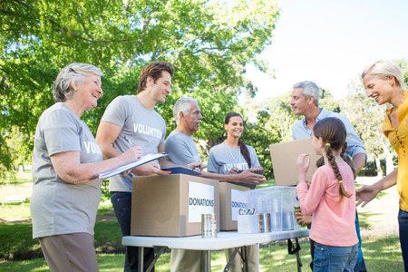 volunteering: Happy volunteer family separating donations stuffs on a sunny day Stock Photo