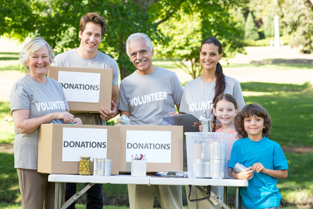 separating: Happy volunteer family separating donations stuffs on a sunny day Stock Photo