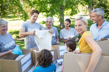 separating: on a sunny dayHappy volunteer family separating donations stuffs Stock Photo
