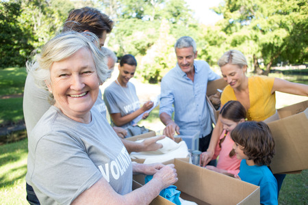 elderly adults: Happy volunteer family separating donations stuffs on a sunny day Stock Photo