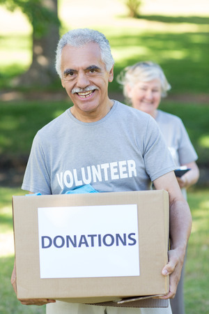 volunteerism: Happy volunteer senior holding donation box on a sunny day